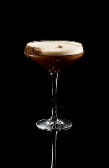 Espresso martini cocktail isolated on a black background.