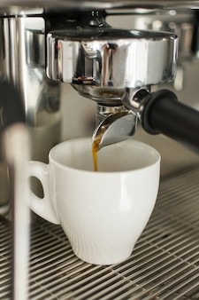 Espresso pouring from coffee machine into one cup