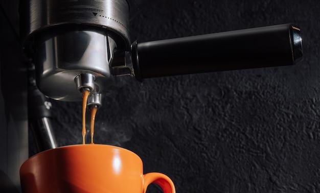 Espresso pouring from coffee machine into orange cup.