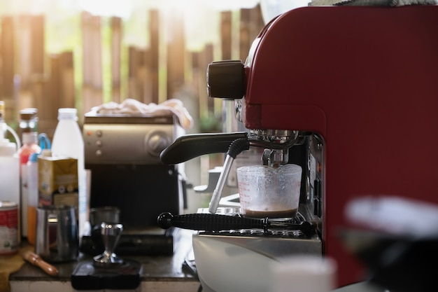 Espresso pouring from coffee machine. professional coffee brewing.