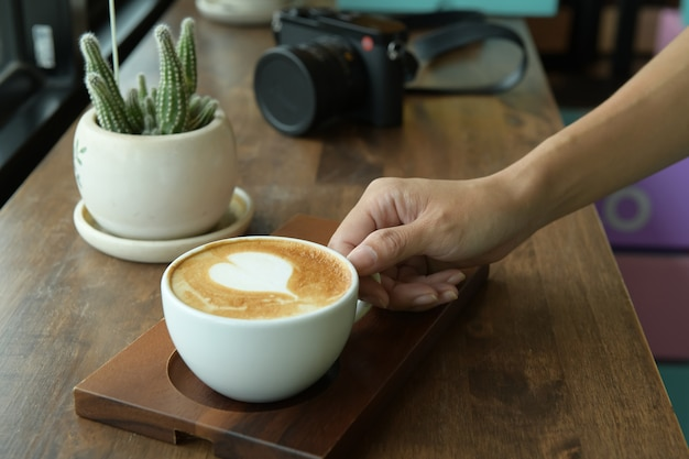 Espresso in white coffee cup with brown wooden table background