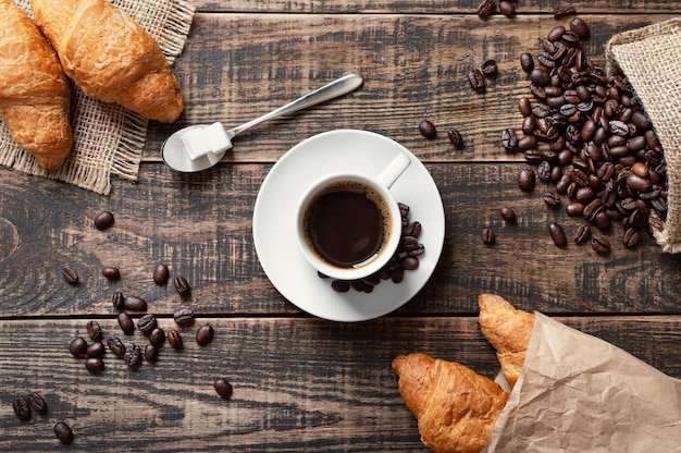 Espresso in a white cup, sugar cubes, coffee beans, freshly baked croissants on a wooden background. the concept of a coffee shop, traditional breakfast, morning ritual. top view, flat lay