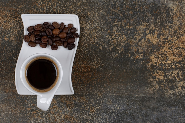 Caffè espresso con chicchi di caffè sul piattino bianco.