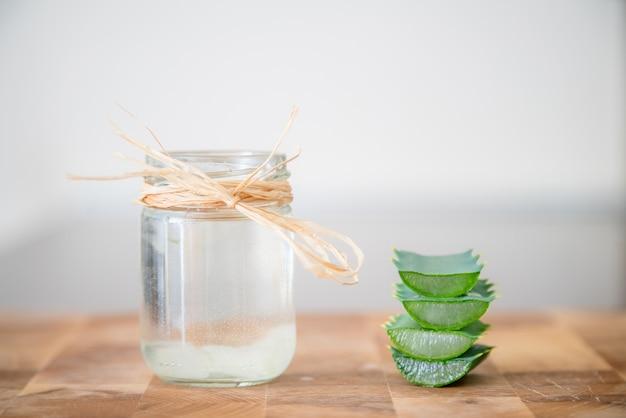 알로에 베라 식물의 에센스를 화장품 병에 담아 식물 조각을 쌓아 놓았습니다.