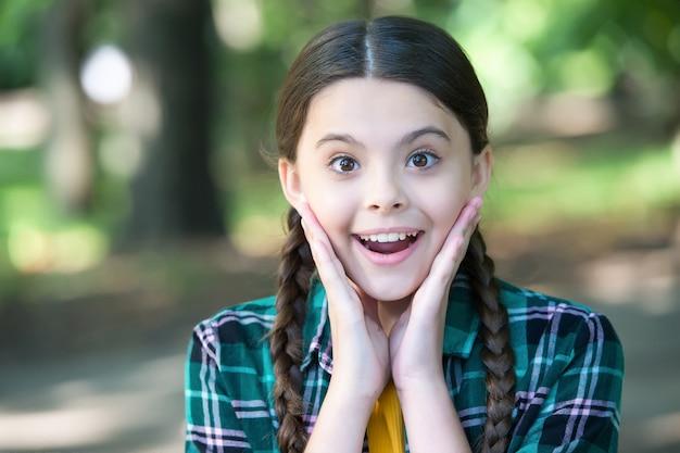 スキンケアのエッセンス。幸せな女の子は屋外で笑顔。ナチュラルスキンケア。小さな子供の美しさの表情。夏のスキンケアルーチン。ベビースキンケア化粧品。あなたはあなたが見るものを気に入るはずです。