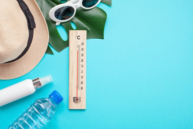 Essential accessories for summer heat: sunglasses, hat, sunscreen and bottle of water. flat lay, top view