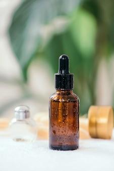 Эфирное ароматическое масло или эссенция сыворотки в бутылке-капельнице из коричневого стекла с пипеткой и зелеными растениями. домашний спа, уход за телом, натуральная органическая косметика.