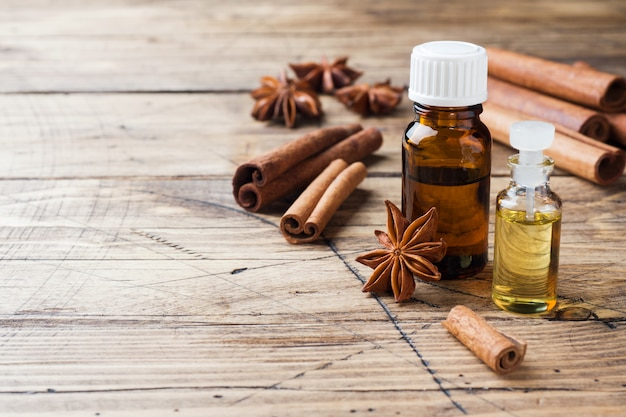 Essential aroma oil with cinnamon and star anise on wooden background.