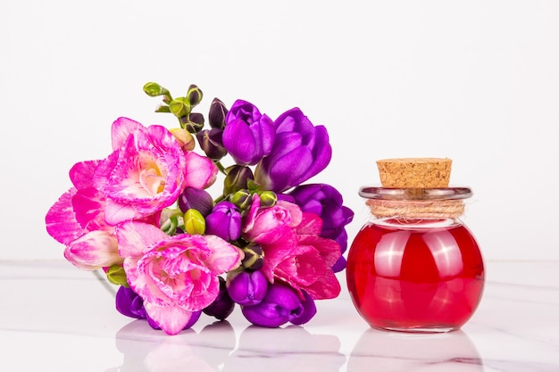 Essential flower oil in a glass jar and pink and purple bouquet on white background