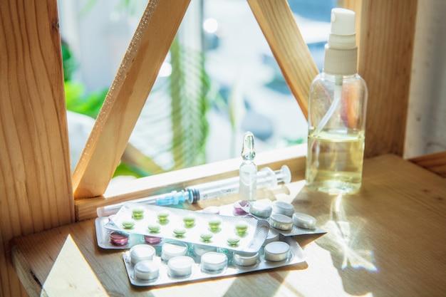エピデミック時の必需品-コロナウイルスの蔓延の防止と保護。呼吸器系を肺炎、covid-19から保護します。消毒剤、フェイスマスク、木製のテーブルの上の丸薬。