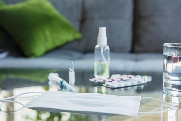 エピデミック時の必需品-コロナウイルスの蔓延の防止と保護。呼吸器系を肺炎、covid-19から保護します。消毒剤、フェイスマスク、テーブルの上に植えます。