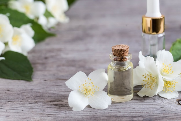 Essential jasmine oil. massage oil with jasmine flowers on a wooden background