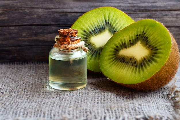 Essential kiwi seed oil in a glass jar with fresh halved kiwifruit on old wooden wall. .aromatherapy,spa,beauty treatment and bodycare concept.selective focus.