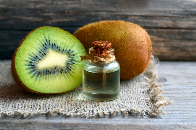 Essential kiwi seed oil in a glass jar with fresh kiwifruit on the table