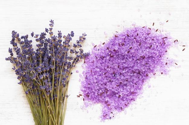 나무 배경에 필수 라벤더 목욕 소금과 라벤더 꽃. spa 라벤더 제품. 부