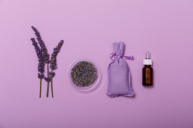 Essential lavender oil and flower with small bag on purple.