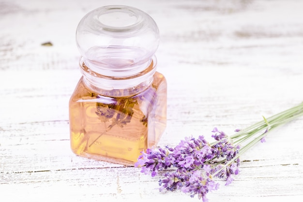 Essential lavender oil and fresh lavender flowers on a background