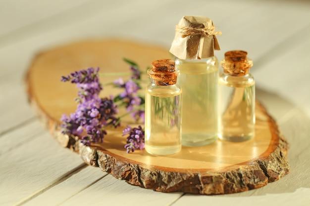 Эфирное лавандовое масло. лавандовое масло устанавливают в прозрачные бутылки и веточки свежей лаванды. чистое органическое масло. ботаническая косметика Premium Фотографии