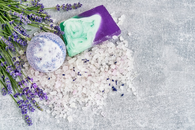 Essential lavender salt, soap and bath bomb with flowers top view. spa lavender products.