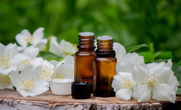 Эфирное масло и цветы жасмина на деревянном фоне. косметические процедуры. выборочный фокус Premium Фотографии