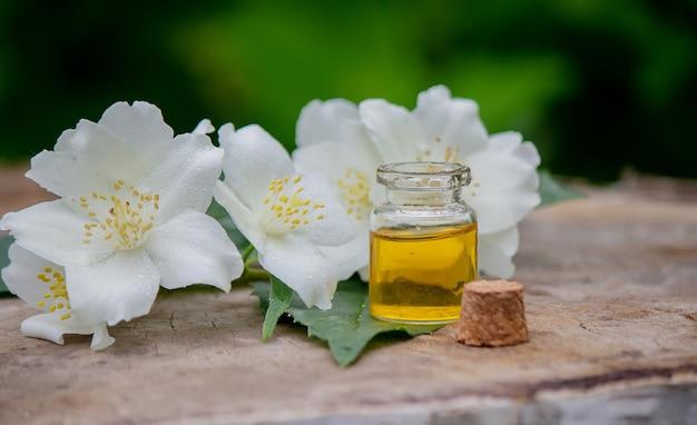 Эфирное масло и цветы жасмина на деревянном фоне. косметические процедуры. выборочный фокус