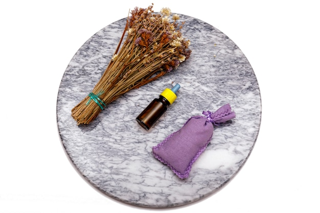 エッセンシャルオイルとラベンダーの花。さまざまなオーガニックハーブと花を使った大理石のテーブルでの精油の選択