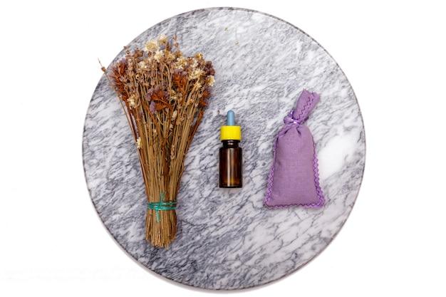 エッセンシャルオイルとラベンダーの花。さまざまなオーガニックハーブと花を使った大理石のテーブルにある精油のセレクション
