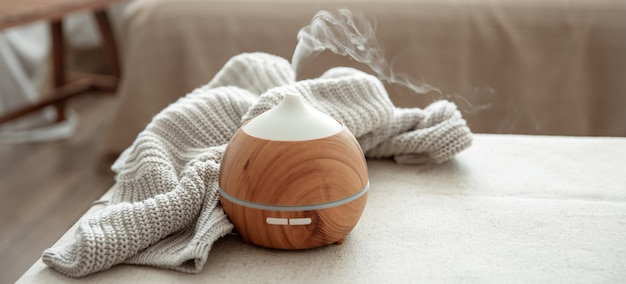 Essential oil aroma diffuser humidifier diffusing water articles in the air copy space.