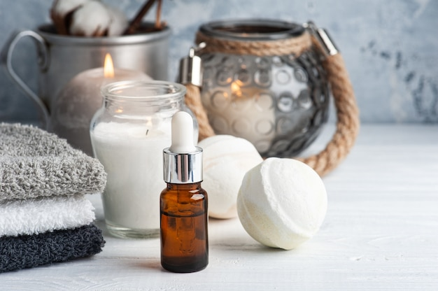 Essential oil and bath bombs in spa arrengement with dry flowers and lit candles