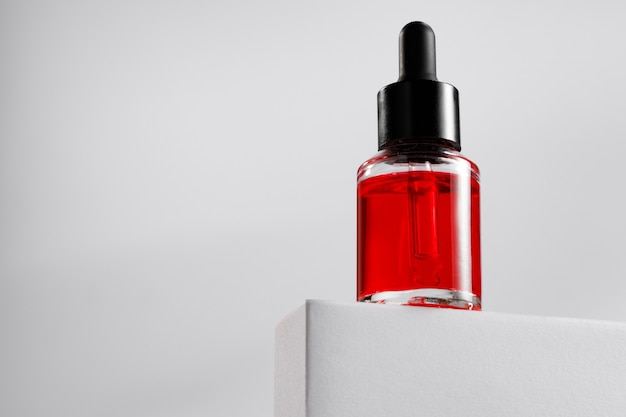 Бутылка эфирного масла на сером блоке на сером фоне крупным планом