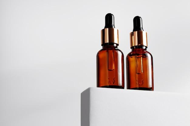 Бутылка эфирного масла на сером блоке на сером фоне