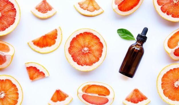 白い背景の上のグレープフルーツのスライスとエッセンシャルオイルのボトル。