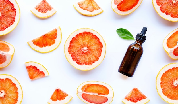 Essential oil bottle with  grapefruit slices on white background.