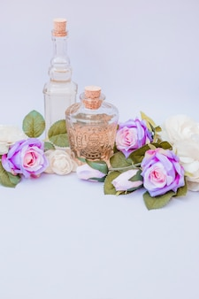 Essential oil bottles and fake roses on white backdrop