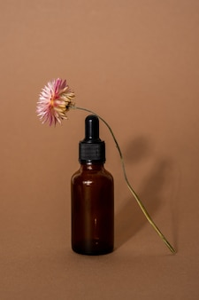 Essential oil in brown glass bottle with pipette and dried flower on beige surface