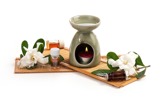 The essential oil burner and cape jasmine flowers are placed on a white.