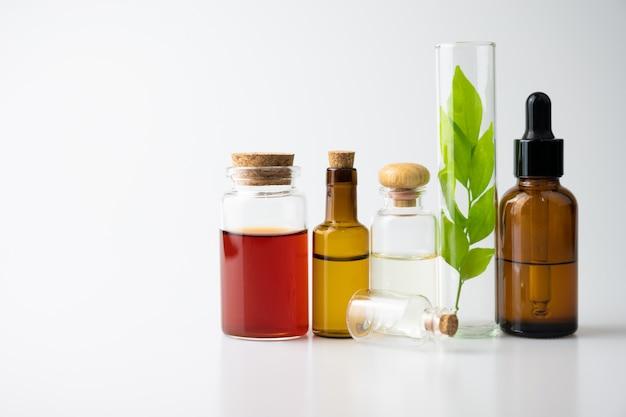 Эфирное масло для ароматерапии в стеклянной бутылке на белом столе, фитотерапия из натуральных
