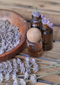 Essential oil from lavender  in bottle and  dried flowers in wooden bowl