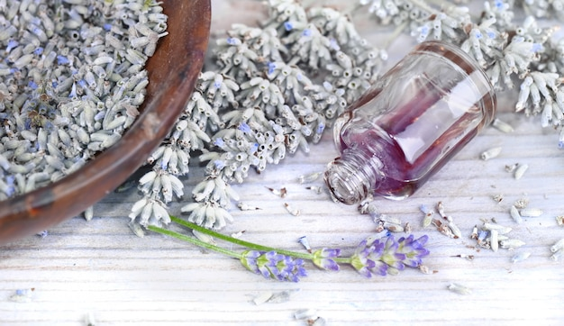 Essential oil from lavender in a overturned bottle and dried flowers
