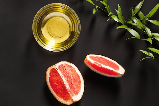 Эфирное масло в стеклянной бутылке со свежим, сочным грейпфрутом и зелеными листьями - косметическая процедура.