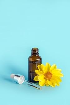 横になっているガラスピペットと青に黄色の花が開いている茶色のドロッパーボトルのエッセンシャルオイル。