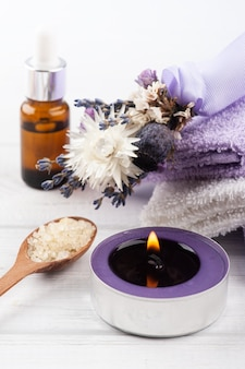 Essential oil and lit lavander candle in spa arrangement with dry flowers and bath salt