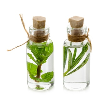 Essential oil made from mint and rosemary isolated on a white background