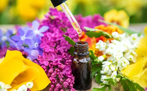 Эфирное масло цветов в бутылочке. выборочный фокус. природа.