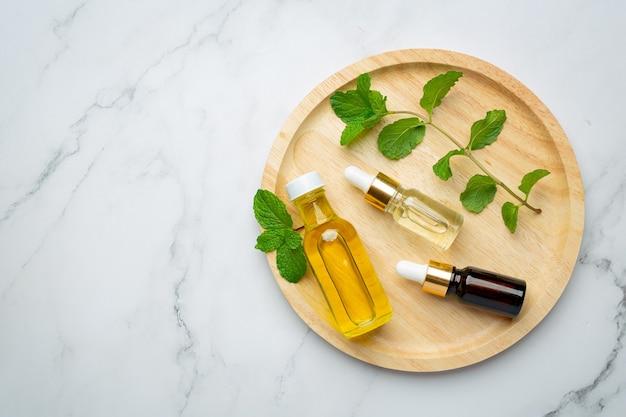 Эфирное масло мяты перечной в бутылке со свежей зеленой мятой