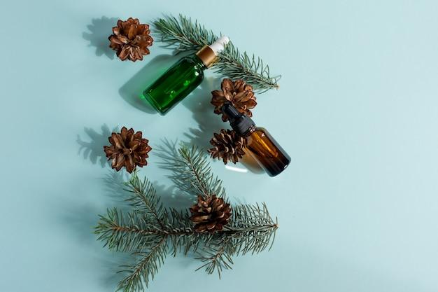 青い背景の上の小さなガラススポイトボトルの松とトウヒのエッセンシャルオイル。