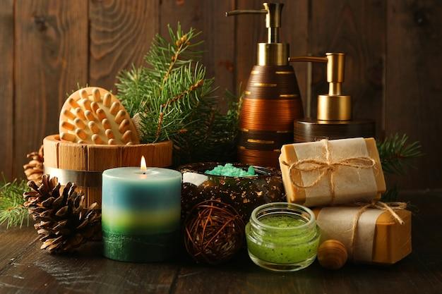 Эфирное масло сосны, мыло ручной работы и крем с экстрактом сосны и спа-процедуры на деревянном