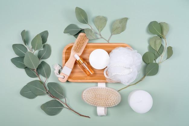에센셜 오일 또는 화장품 세럼 병, 마사지 브러쉬, 천연 유칼립투스 잎이있는 녹색 배경에 얼굴 크림