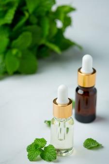 Olio essenziale di menta piperita in bottiglia con menta piperita verde fresca