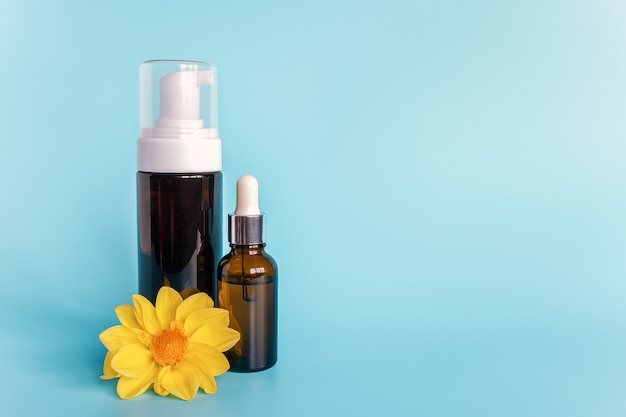 Essential oil in small open brown dropper bottle with lying glass pipette, big bottle with white dispenser and yellow flower on blue